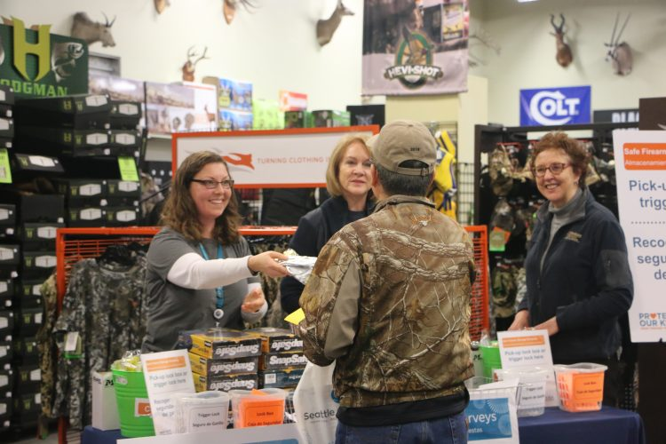 Handing information to a participant at gun safety event