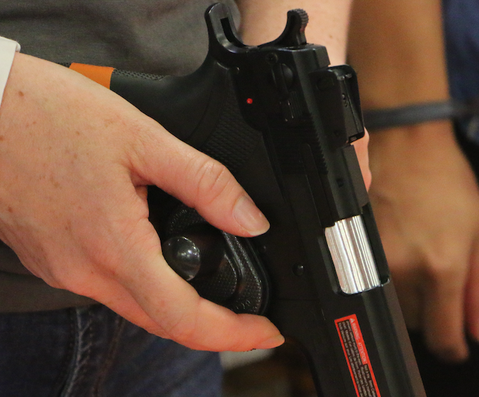 A woman demonstrates how to use a gun safety lock, which is over the gun's trigger