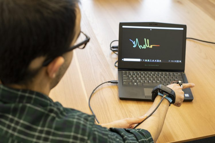 A researcher writes 'hello' on a computer screen by drawing out the letters in the air with a finger. The researcher is wearing the ring/wristband combo.