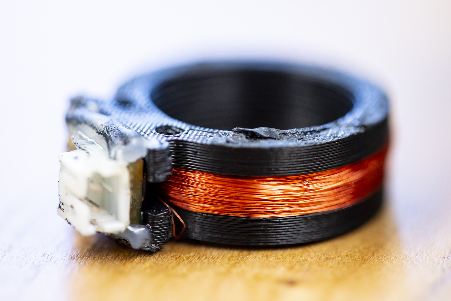 The ring is black plastic with orange copper wire coiled around it