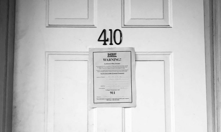 Photo of closed door with eviction notice on the front