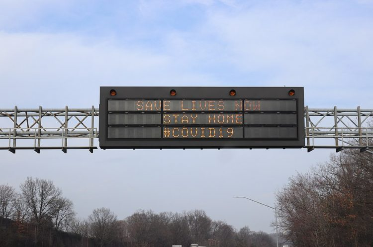 Digital sign says Save Lives Now Stay Home COVID-19