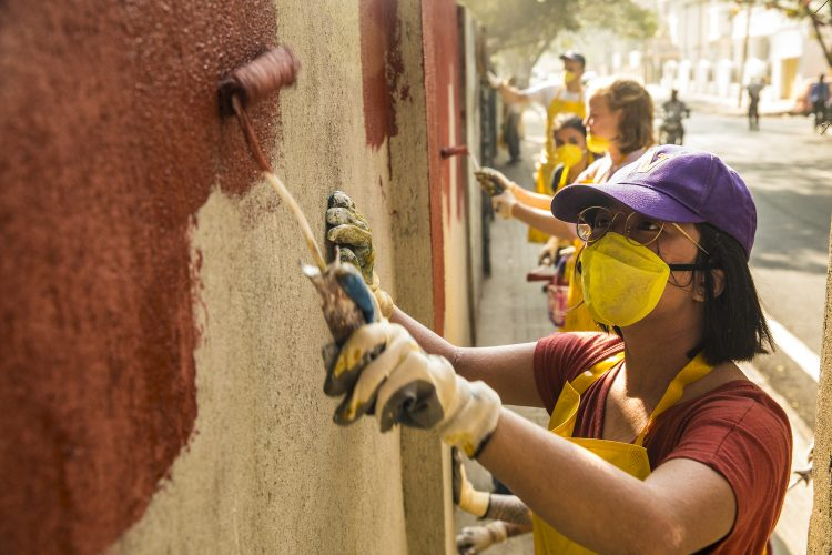 Students painting a wall a copper color