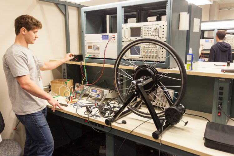 A student in a lab watching a bike wheel on a track