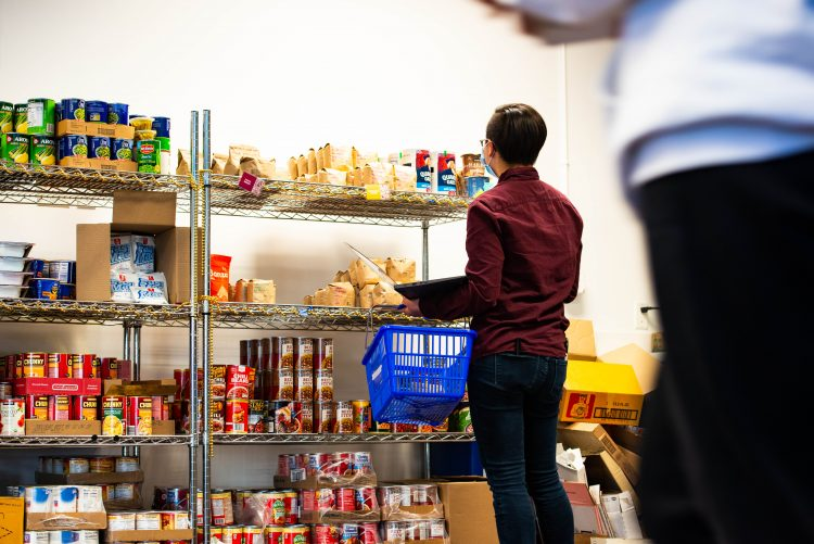 Person standing in front of shelves of food, carrying a shopping basket.