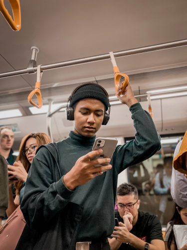 A person on a train looking at their phone. Other people are on their phones behind that person.