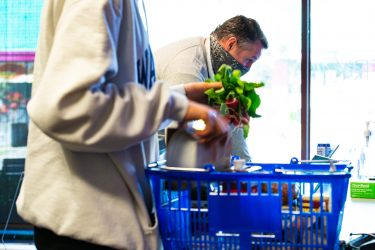 person placing radishes in a blue shopping basket
