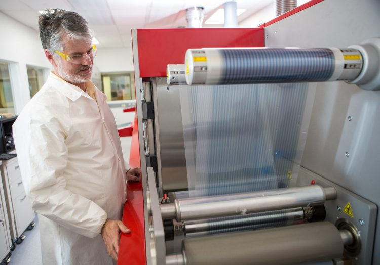 A person inside a laboratory demonstrating printer technology for flexible electronics