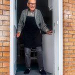 Elderly man opening front door to find a bag of food on his doorstep