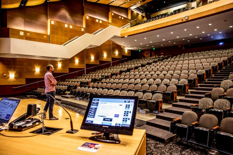 man on stage in empty auditorium