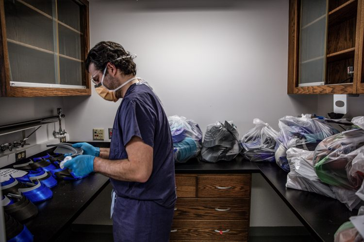 man in scrubs disinfects visors that affix to face shields