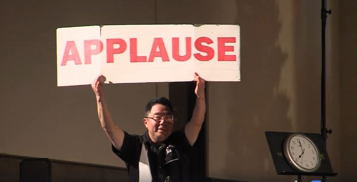 "Curtis Takahashi reminds the audience to applaud in a Seattle Radio Theater production of ""The Bishop's Wife"" at Town Hall Seattle, broadcast by KIRO TV."