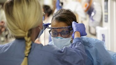 health care workers helps take protective glasses off another