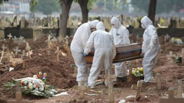people in hazmat suits put a coffin in the ground