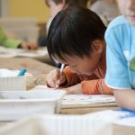 Young boy coloring at a classroom table