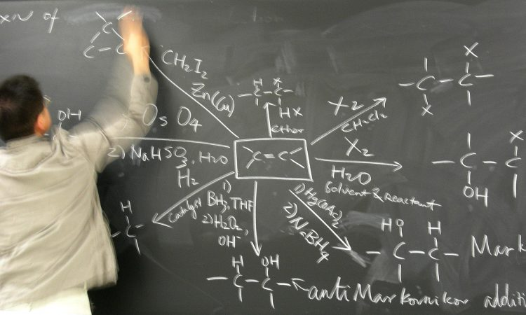 A person at a chalkboard delivering a chemistry lecture