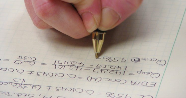 A person writing chemistry notes down on a piece of paper.