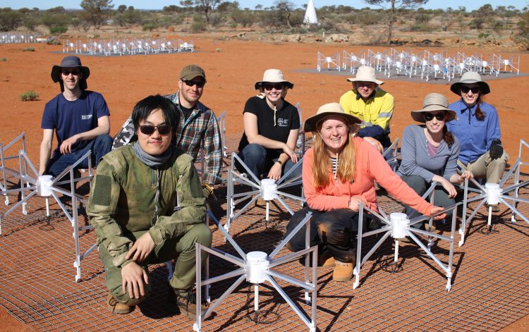 An image of scientists in the Australian desert as they assemble parts for a radio telescope.