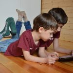 Two boys lying on floor, looking at tablet screen