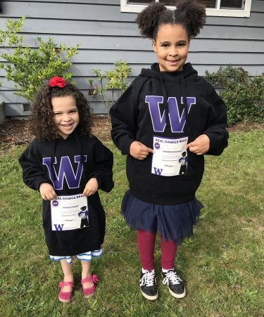 Two girls, age 4 and 7, hold certificates and wear University of Washington hoodies