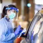 A UW Medicine worker wearing personal protective equipment stands outside a car at a drive up testing clinic