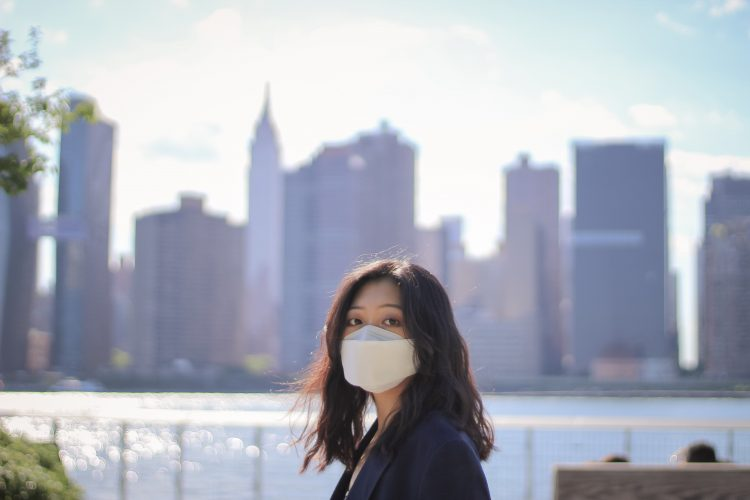 Person wearing a face mask with New York City skyline in the background
