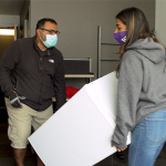 Man and young woman carry small fridge into dorm room