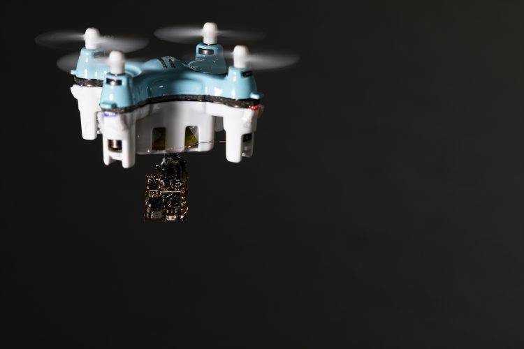 A drone flying and carrying a small sensor chip beneath it.