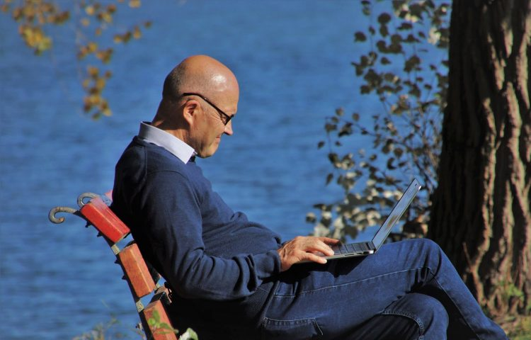 older man sitting on park bench with laptop