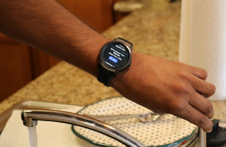 A hand turning off a faucet. There is a smartwatch on the person's wrist that is giving information about the sound of the water in the sink.