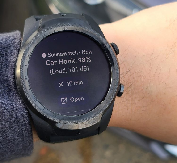 "A wrist with a smartwatch on it. The smartwatch has an alert that says ""Car honk, 98%, Loud, 101 dB"" It also has options to snooze the alert for 10 minutes or open in an app on the user's phone."