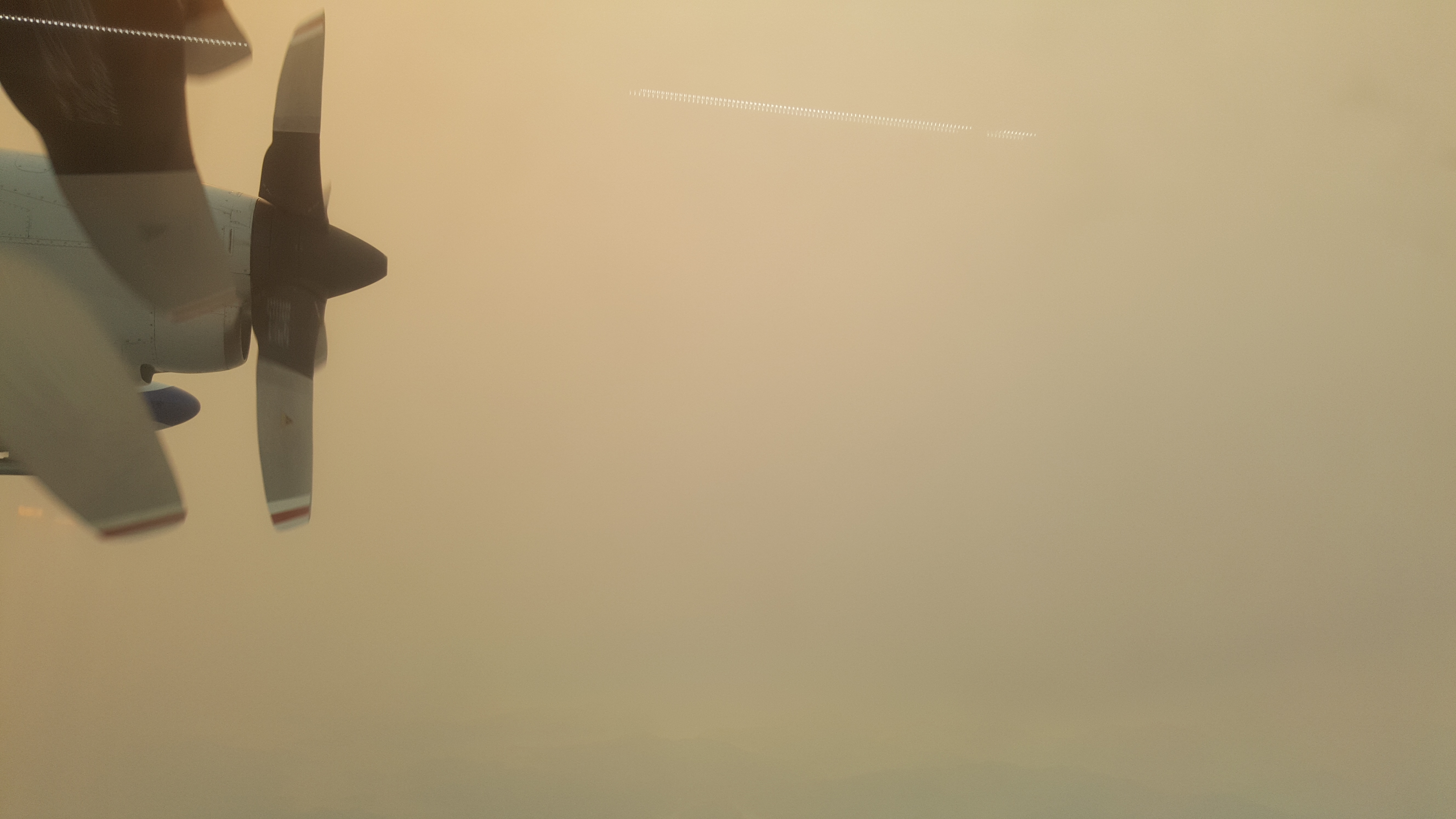 A plane propeller is visible in thick yellow/brown smoke