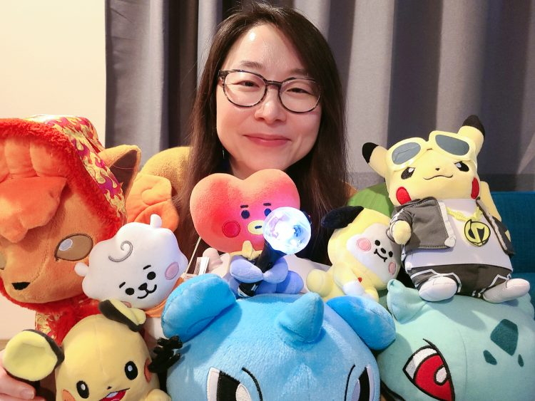 A portrait of a researcher surrounded by stuffed Pokémon