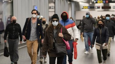 people in masks walk through airport