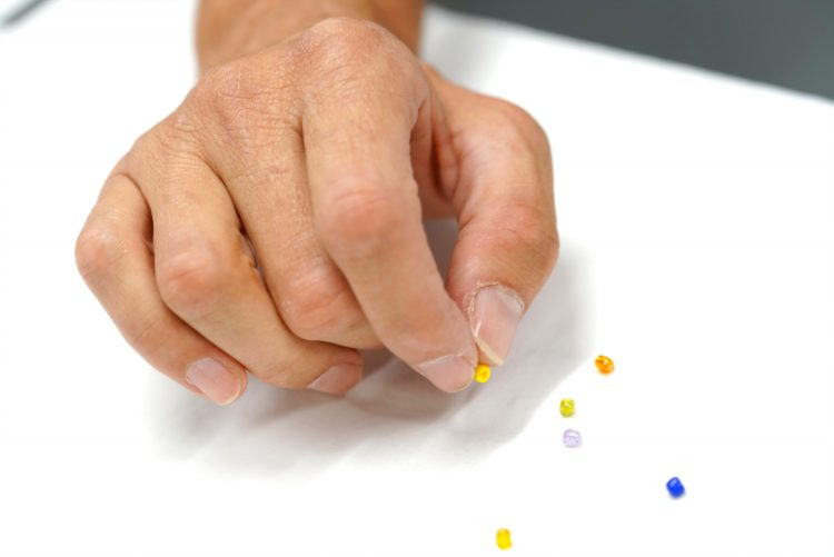 A hand picking up a tiny bead