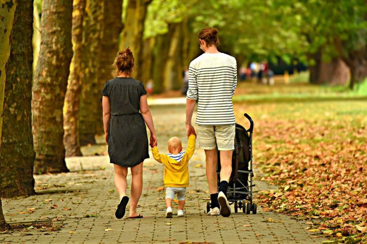 parents with young child walking in a park