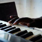A hand pressing a piano key