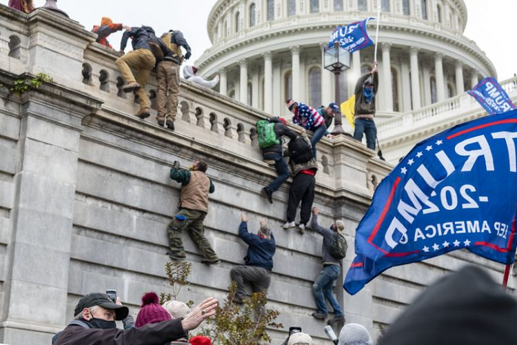 Rioters scaling the wall at the U.S. Capitol