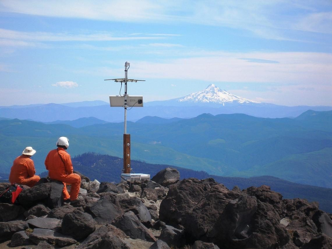 scientists in orange suits with mountains in distance