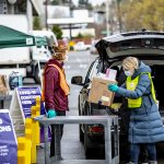 Woman gives a box of masks to a donation drive at a UW parking lot.