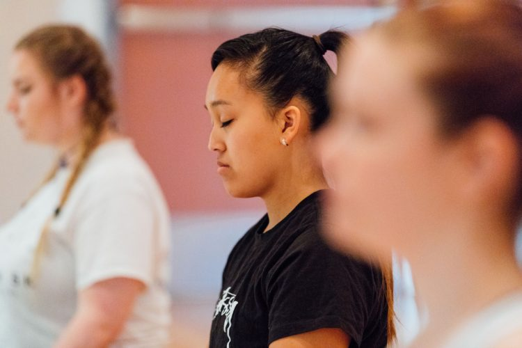 Students standing silently, eyes closed, in a yoga or meditation class
