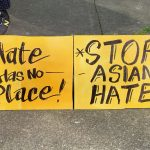 "Signs read ""hate has no place"" and ""stop Asian hate"""