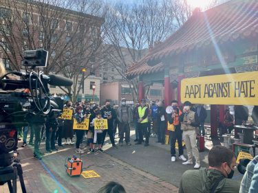 TV cameras pointed to people standing under a banner that reads AAPI Against Hate