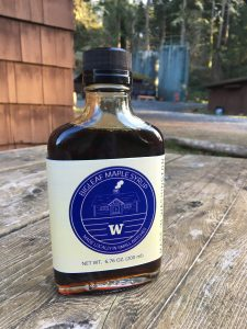A bottle of maple syrup with a purple label sitting on a weathered wood tabletop.