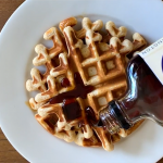 Maple syrup is being poured on a round waffle on a white plate.