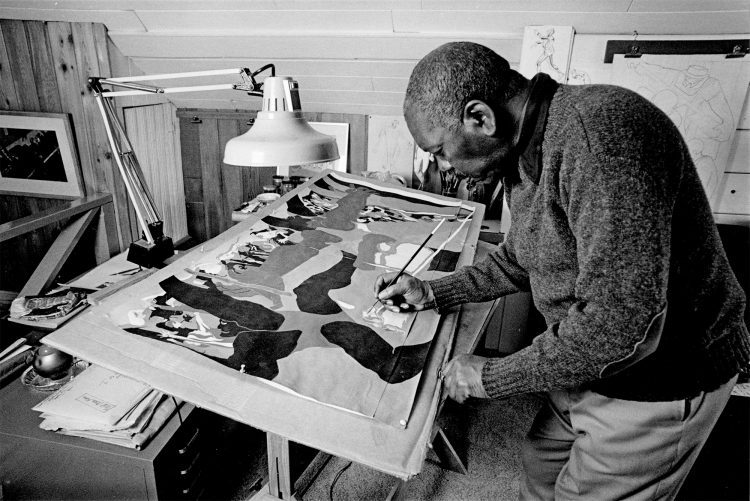 Jacob Lawrence painting in his studio