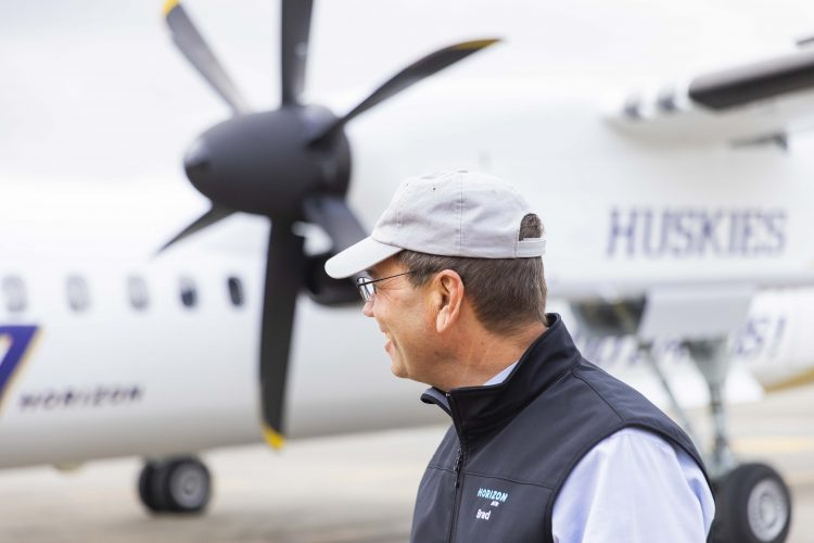 Brad Tilden, a UW alum who retired as CEO of Alaska Airlines on March 31, looks at a Horizon Air Q400 aircraft with a special UW-themed livery.