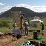 A group of men on a hill erecting a solar panel, part of seismic site being constructed in Enumclaw, Wa