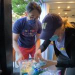 Student volunteers look at medical supplies inside a van.