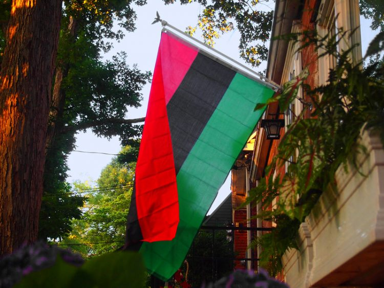A red, black and green flag hangs outside a building.